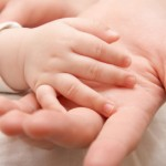 The hand of the child gently lays in a hand of mother